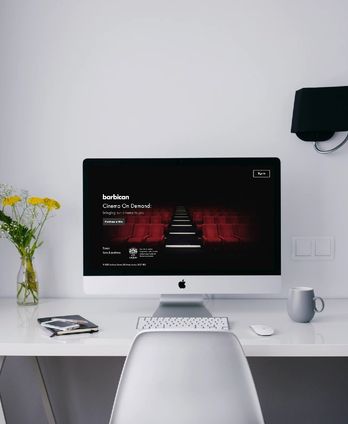 Mockup of the Barbican Cinema On Demand splashpage on a Mac in a home office